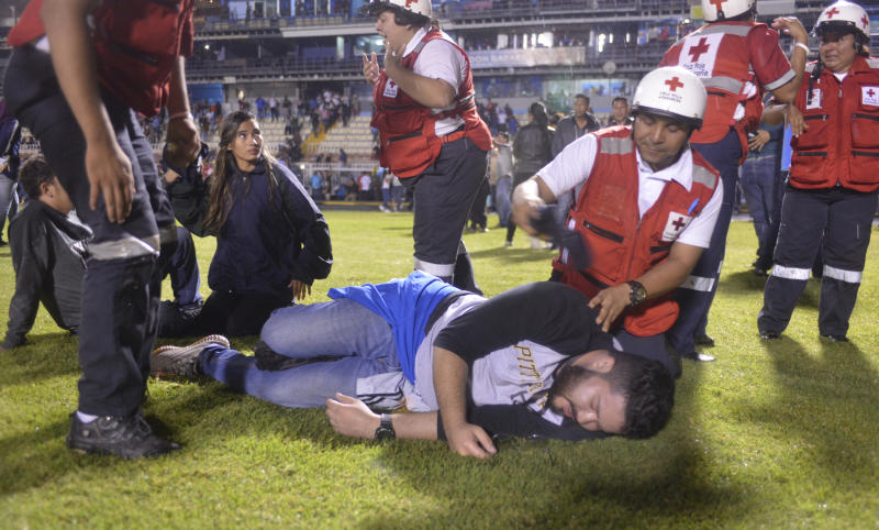 Soccer fans affected by tear gas fired by police are helped by members of the Red Cross after a deadly fight broke out between fans before the start of a game between Motagua and Olimpia, inside the national stadium in Tegucigalpa, Honduras, late Saturday, Aug. 17, 2019. The fight between fans of rival soccer teams outside the stadium left three people dead and led to the suspension of the game. (Victor Colindres/La Tribunal via AP)