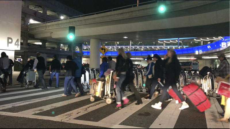 FILE - In this Wednesday, Dec. 21, 2016, file photo shows travelers leaving a terminal at Los Angeles International Airport. At the end of the month, travelers will not be able to hail a rideshare or taxi outside terminals at Los Angeles International Airport. LAX announced Friday, Oct. 4, 2019, that travelers will instead have to take shuttles or walk to a special location outside the central terminal area where they can be picked up.(AP Photo/Damian Dovarganes,File)
