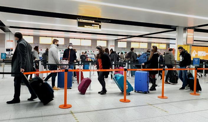 Passengers queue for check-in at Gatwick Airport in West Sussex, amid concerns that borders will close and with the public being urged to adhere to Government guidance after Prime Minister Boris Johnson announced on Saturday that from Sunday areas in the South East currently in Tier 3 will be moved into a new Tier 4 for two weeks Ð effectively returning to the lockdown rules of November, after scientists warned of the rapid spread of the new variant coronavirus. (Photo by Gareth Fuller/PA Images via Getty Images)