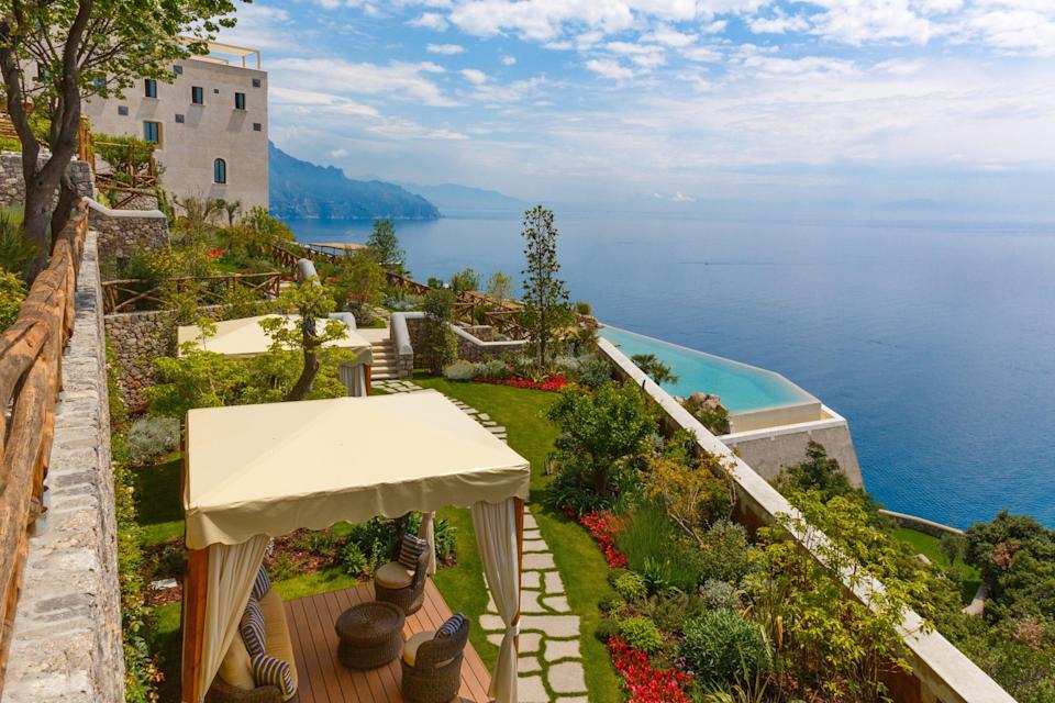 """We all dream of a romantic, <a href=""""https://www.cntraveler.com/galleries/2014-02-20/stunning-italian-coastal-towns?mbid=synd_yahoo_rss"""" rel=""""nofollow noopener"""" target=""""_blank"""" data-ylk=""""slk:seaside Italian getaway"""" class=""""link rapid-noclick-resp"""">seaside Italian getaway</a> and this one just might be it. The hotel occupies a restored 17th-century monastery just three miles from Amalfi. With 20 rooms, terraced gardens, clifftop Mediterranean views, and a pool that seems to float over the sea, you'll find yourself right at that point of enjoying the seclusion without feeling isolated. Stroll the four levels of terraced gardens, and don't miss the spa, which includes sauna and steam rooms, a hydro pool, and tepidarium. You can enjoy a martini with a side of chess at the library and bar before dining on local Campanian specialties at Il Refettorio, the Michelin-starred restaurant, where the charming servers are straight out of central casting. They still make sfogliatelle (sweet, shell-shaped, filled pastries) according to the nuns' original recipe—a treat to savor with the sweet life on offer here."""