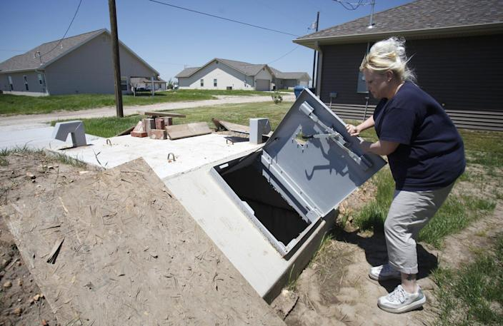 Tracy Anderson opens her storm shelter on May 14, 2013 that she had installed behind her new house in Joplin, Mo. Her home was destroyed in the May 22, 2011, tornado that ravaged Joplin.