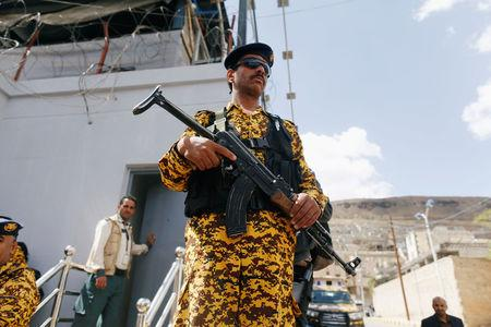 Police trooper stands guard as wounded Houthi fighters demonstrate outside the United Nations offices to demand for medical  treatment abroad, in Sanaa, Yemen