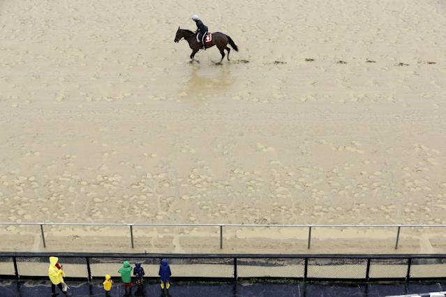 Spectators clad in raincoats watch a horse walk along a sloppy track as rain falls at Pimlico Race Course in Baltimore, Friday, May 16, 2014. The Preakness Stakes horse race is scheduled to take place May 17. (AP Photo/Patrick Semansky)
