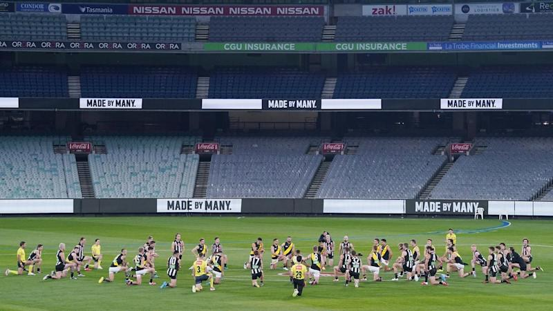 Collingwood and Richmond players kneel together before their AFL season-resuming match at the MCG