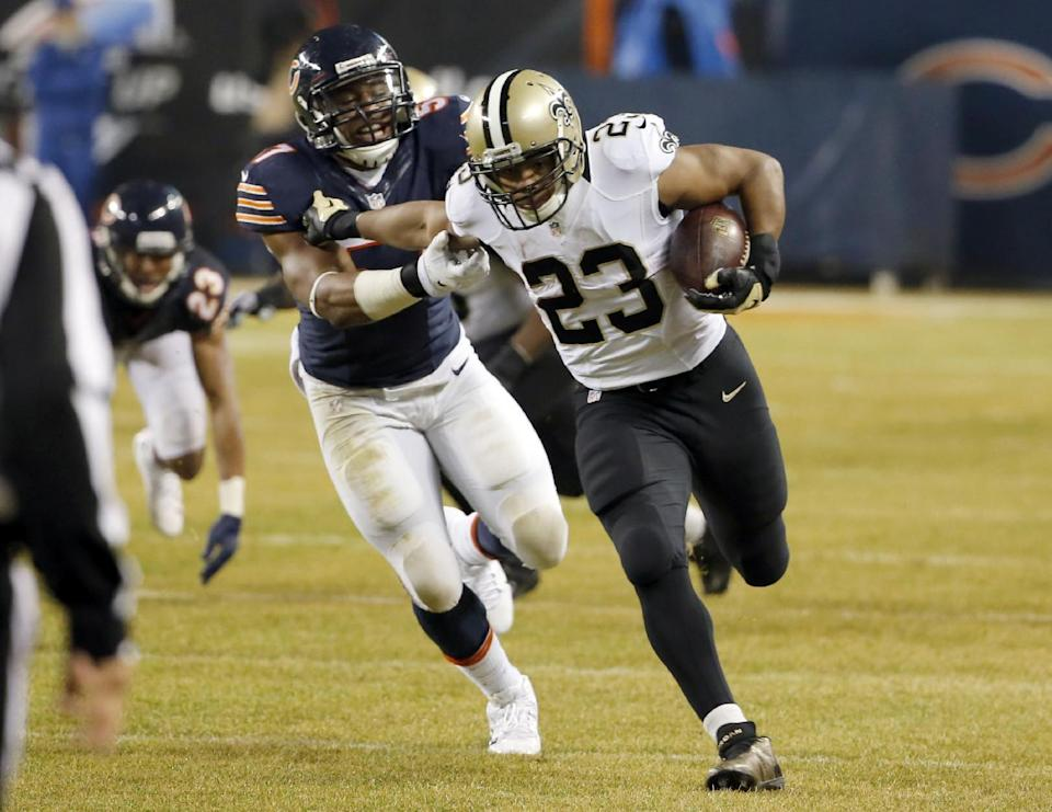 New Orleans Saints running back Pierre Thomas (23) carries the ball against Chicago Bears outside linebacker Jon Bostic (57) during the first half of an NFL football game Monday, Dec. 15, 2014, in Chicago. (AP Photo/Charles Rex Arbogast)