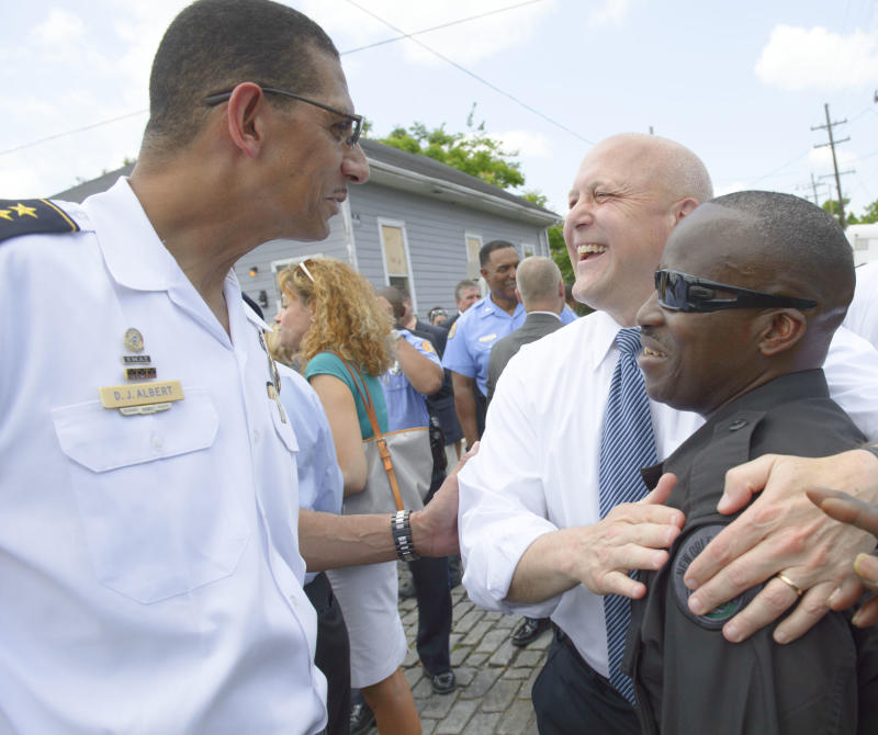 Darryl J. Albert, New Orleans Police Department Deputy Superintendent, left smiles as New Orleans Mayor Mitch Landrieu congratulates SWAT Team member Frankie Watts Sr. after at a news conference at North Villere and Frenchman Streets in New Orleans, Thursday, May 16, 2013, about two recent arrests made in the Mother's Day parade shooting.  Two brothers with a history of drug arrests and ties to a neighborhood gang each face 20 counts of attempted second-degree murder in a shooting spree that brought a sudden bloody end to the neighborhood Mother's Day parade. (AP Photo/Matthew Hinton)