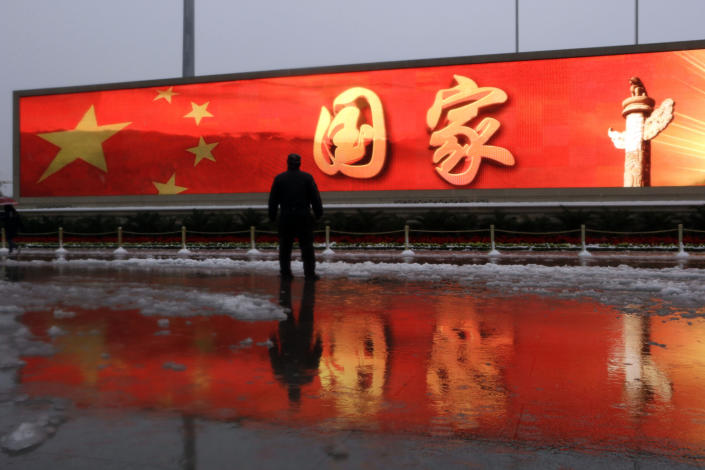 """In this photo taken Sunday, Nov. 4, 2012, a Chinese man stands near a screen displaying the Chinese national flag colours and the word """"Nation"""" near the Great Hall of the People where the Chinese Communist Party's 18th National Congress is scheduled to begin Nov. 8 in Beijing, China. Authorities want no more surprises as party leaders convene in the capital, and rights groups say the wide-ranging crackdown on critics bodes poorly for those who hope the incoming generation of leaders will loosen restrictions on activism. (AP Photo/Ng Han Guan)"""