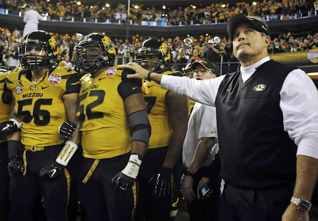 FILE - In this Jan. 3, 2014 file photo, Missouri head coach Gary Pinkel, right, and players, including offensive linesman Robert Luce (56) and defensive lineman Michael Sam (52), prepare to take the field for the Cotton Bowl NCAA college football game against Oklahoma State, in Arlington, Texas. Michael Sam hopes his ability is all that matters, not his sexual orientation. Missouri's All-America defensive end came out to the entire country Sunday night, Feb. 9, 2014, and could become the first openly gay player in America's most popular sport. (AP Photo/Tim Sharp, File)