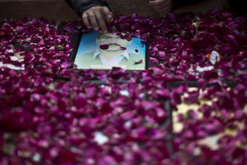 Photographs of missing people are covered with rose petals during a march in Rawalpindi, Pakistan, Friday, Feb. 28, 2014. Affected families walked nearly 3,000 kilometers to reach capital Islamabad and register protest against the abductions and killings of their loved ones by Pakistani security agencies without producing them in court of law. (AP Photo/Muhammed Muheisen)