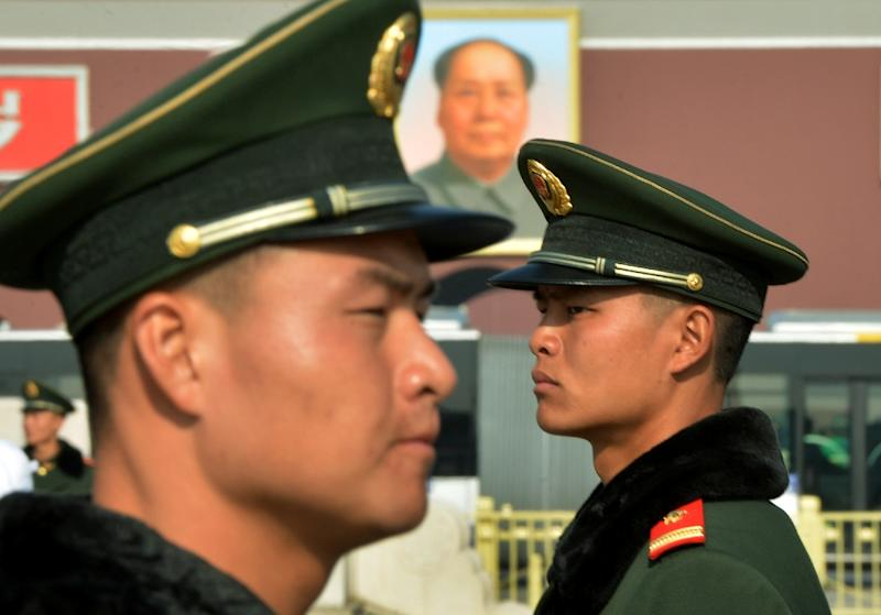 Chinese paramilitary police stand guard in front of the portrait of late leader Mao Zedong at Tiananmen Square in Beijing on November 6, 2012