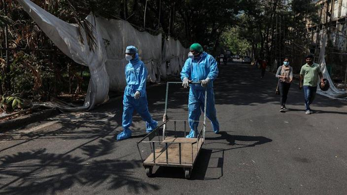 Health workers wearing personal protective equipment walk pass a quarantine centre in Mumbai, India, 12 April 2021.