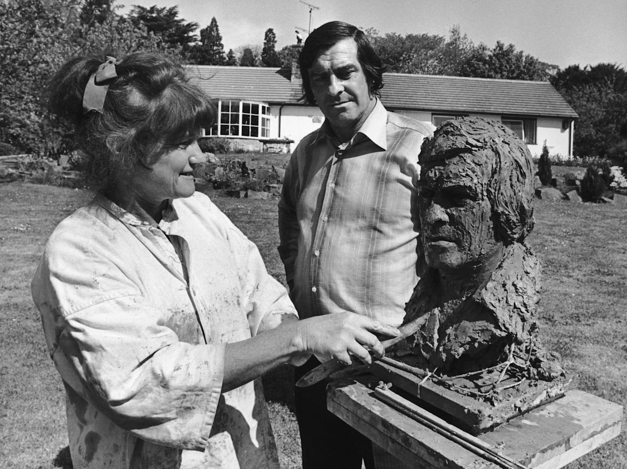Ace bowler Fred Trueman (1931 - 2006) looks on as sculptor Betty Miller works to complete a bust of him, in the garden of his Gargrave home, 10th June 1977. (Photo by Keystone/Hulton Archive/Getty Images)