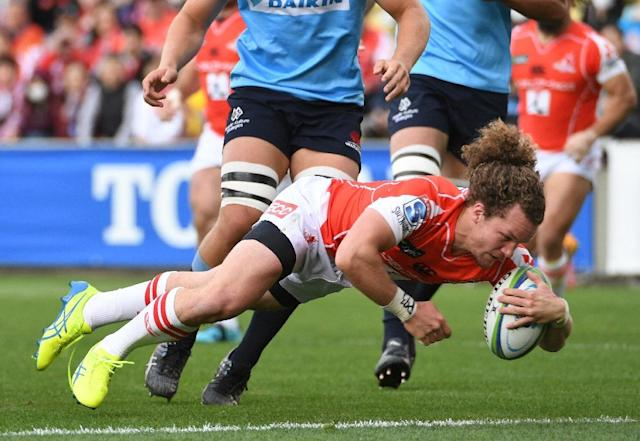 Michael Little of the Sunwolves (C) dives to score a try during the Super Rugby union match between the Sunwolves of Japan and the Waratahs of Australia (AFP Photo/Toshifumi KITAMURA)