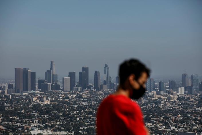Izzy Galvan, 20, wears a face mask while visiting the Griffith Observatory overlooking downtown Los Angeles, in July.