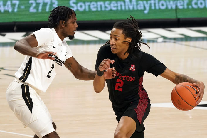 Houston guard Caleb Mills, right, drives around Central Florida guard Darius Perry, left, during the second half of an NCAA college basketball game, Saturday, Dec. 26, 2020, in Orlando, Fla. (AP Photo/John Raoux)