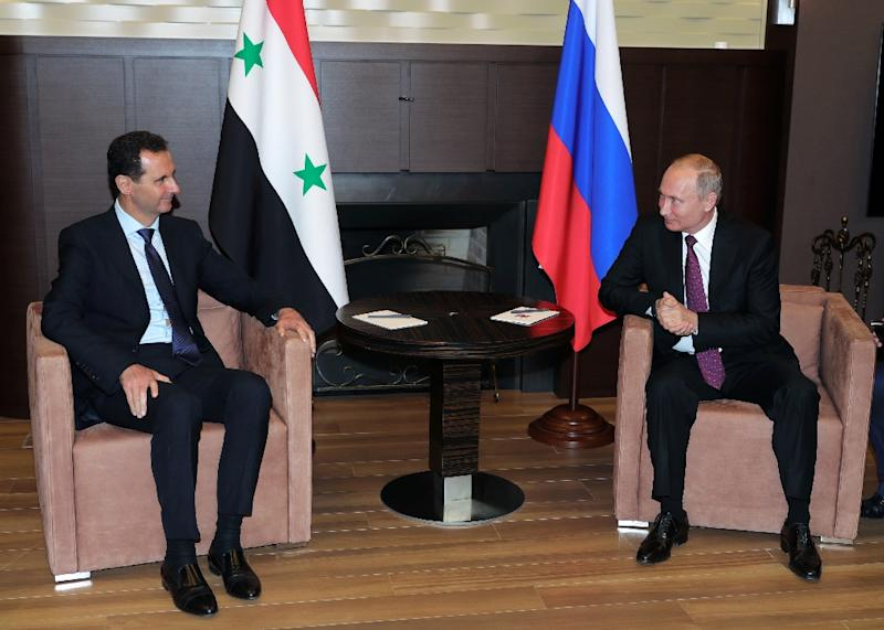 Russian President Vladimir Putin (R) speaks with his Syrian counterpart Bashar al-Assad during their meeting in Sochi