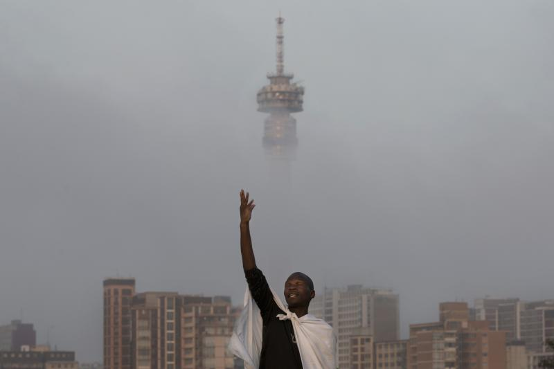 A Christian worshipper prays on a hill overlooking the city of Johannesburg, South Africa, Sunday, Dec. 8, 2013. South Africans flocked to houses of worship for a national day of prayer and reflection to honor former President Nelson Mandela, starting planned events that will culminate in what is expected to be one of the biggest funerals in modern times. (AP Photo/Bernat Armangue)