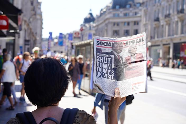 """<p>A woman holding a newspaper in NHS rally, which showing Mr. Trump and Mrs. May with the title """"shut down trump's UK visit, June 30, 2018. (Photo: Escapade Leo/Shutterstock) </p>"""