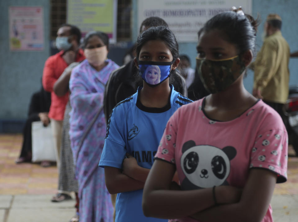 People wait in a queue give their nasal swab samples to test for COVID-19 in Hyderabad, India, Saturday, Aug. 22, 2020. India has the third-highest caseload after the United States and Brazil, and the fourth-highest death toll in the world. (AP Photo/Mahesh Kumar A.)