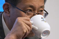 Yao Hui, Beijing's Winter Olympic Games organizing committee official in charge of venues, drinks from a cup during a press conference in Beijing Monday, Oct. 4, 2021. Beijing organizers on Monday announced a series of new test events. This schedule comes days after organizers and the IOC published rigid restrictions at the Games for athletes and everyone else, controls that apparently have the full support of the IOC. (AP Photo/Ng Han Guan)