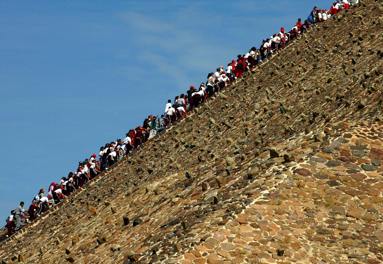 MEXICO CITY- NOVEMBER 15:  Sight-seers climb the site of the ancient Sun Pyramid at the Teotihuacan Citadel outside of Mexico City during the Gran Premio Gigante-Telmex, round 19 of the CART (Championship Auto Racing Teams) Fed Ex Championship Series on November 15, 2002  at the Autodromo Hermanos Rodriguez in Mexico City, Mexico. (Photo by Donald Miralle/Getty Images)