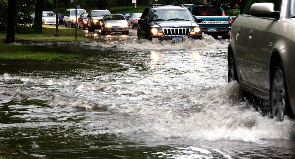 Cars driving on Dean Parkway in Minneapolis, USA, through flood waters.