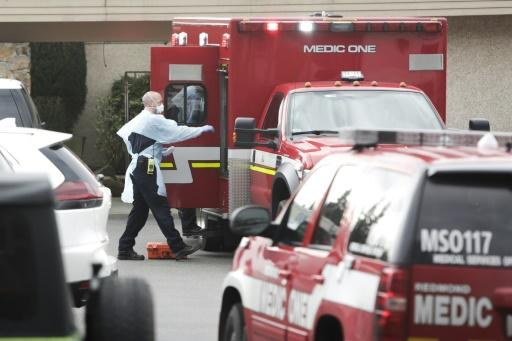 Ambulance staff prepare to transport a patient from the Life Care Center nursing home where some residents have died from COVID-19 in Kirkland, Washington on March 5, 2020