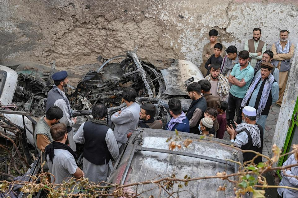 TOPSHOT - Afghan residents and family members of the victims gather next to a damaged vehicle inside a house, day after a US drone airstrike in Kabul on August 30, 2021.  / AFP / WAKIL KOHSAR