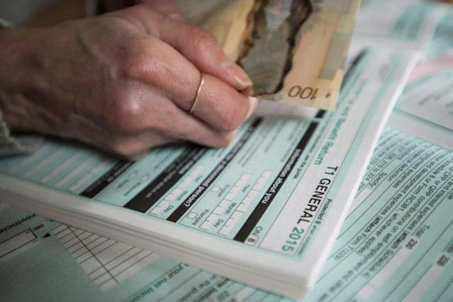 Tax forms and Canadian currency are shown together in a photo illustration taken in Toronto on Sunday, April 3, 2016. (THE CANADIAN PRESS/Graeme Roy)