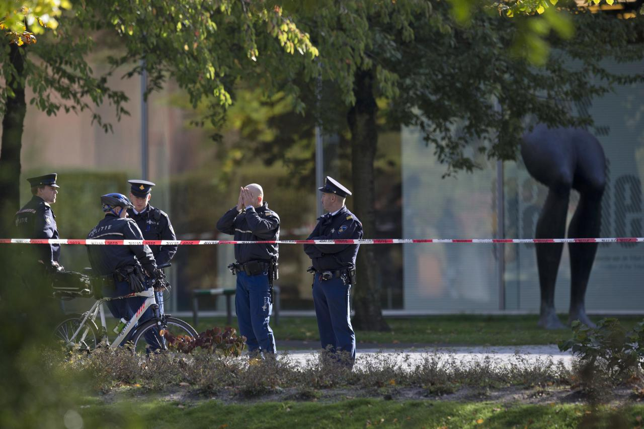 "Police officers guard a cordoned off area at the rear side of the Kunsthal museum in Rotterdam, Tuesday Oct. 16, 2012. Several paintings have been stolen from a museum in the Dutch city of Rotterdam that was exhibiting works by Pablo Picasso, Henri Matisse and Vincent van Gogh. At least several paintings were stolen early Tuesday morning from the Kunsthal museum , but their names have not yet been released. They are believed to include at least one by Henri Matisse, the 1919 ""Reading Girl."" (AP Photo/Peter Dejong)"