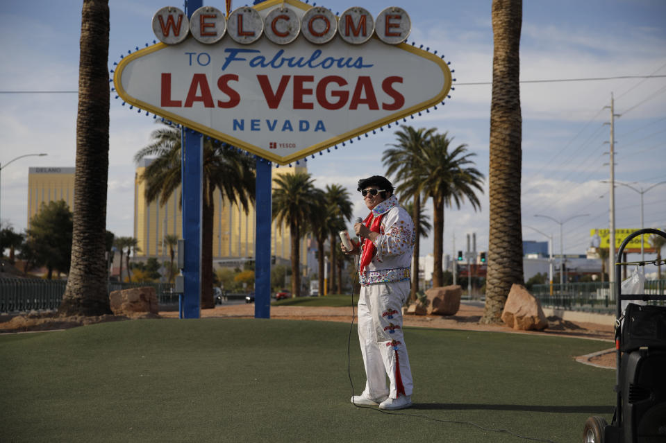 """In this April 16, 2020, photo, Chris Morehouse drinks a beer while performing as Elvis at the """"Welcome to Fabulous Las Vegas Nevada"""" sign along the Strip in Las Vegas. """"I'm just singing for the sign,"""" said Morehouse who was at times performing save the few locals who occasionally took advantage of the eerie silence to take photos at the sign. (AP Photo/John Locher)"""