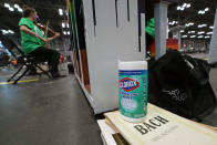 A container of disinfecting wipes sits on Bach sheet music as violist Rachel Golub, left, plays in a piano quintet at the Jacob K. Javits Convention Center, Thursday, March 18, 2021, in New York. (AP Photo/Kathy Willens)