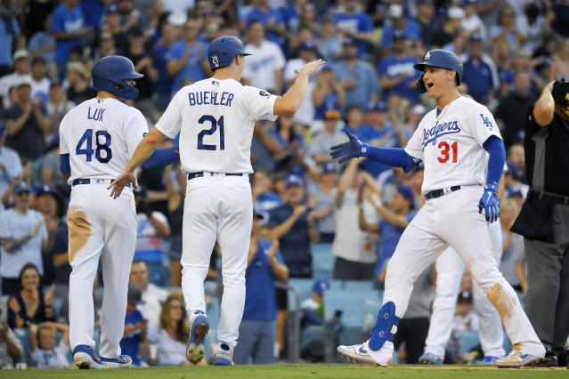 Los Angeles Dodgers' Joc Pederson, right, is congratulated by Walker Buehler, center, and Gavin Lux after hitting a three-run home run during the third inning of a baseball game against the Colorado Rockies Monday, Sept. 2, 2019, in Los Angeles. (AP Photo/Mark J. Terrill)