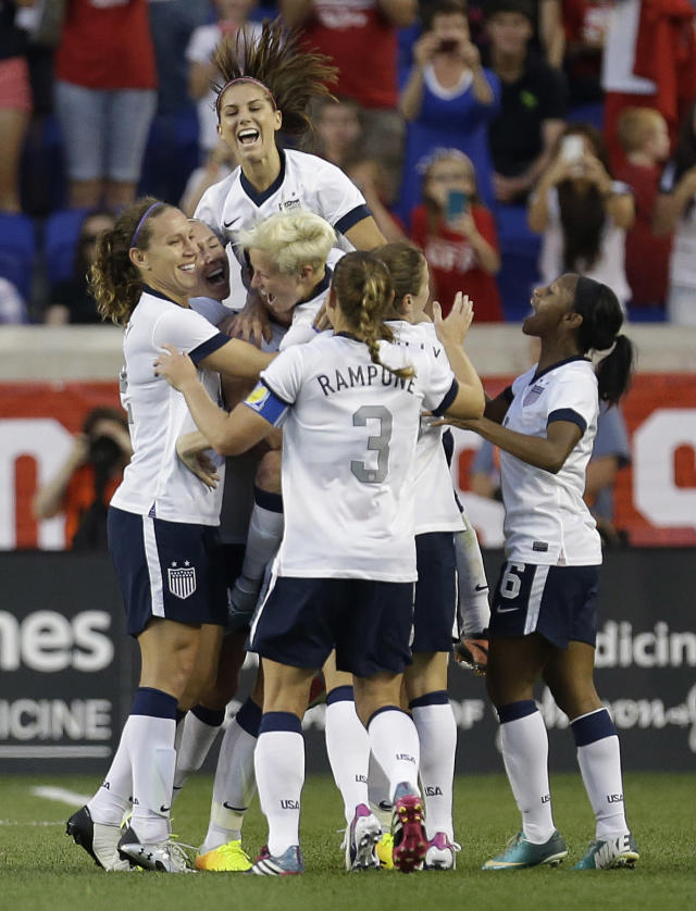 United States women soccer players mob Abby Wambach after she scored a goal against South Korea during the first half of an international friendly soccer match at Red Bull Arena, Thursday, June 20, 2013, in Harrison, N.J. With the goal, Wambach broke Mia Hamm's national goal-scoring record. (AP Photo/Julio Cortez)