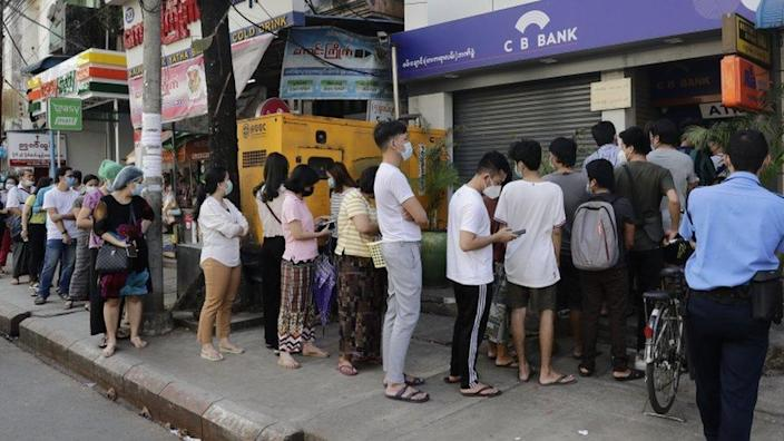 Myanmar people line up in front of a ATM machine of a closed bank in Yangon, Myanmar, 01 February 2021