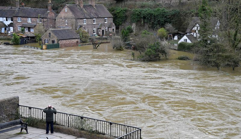 FILE PHOTO: A man views flooded properties beside the River Severn in Ironbridge, Britain,