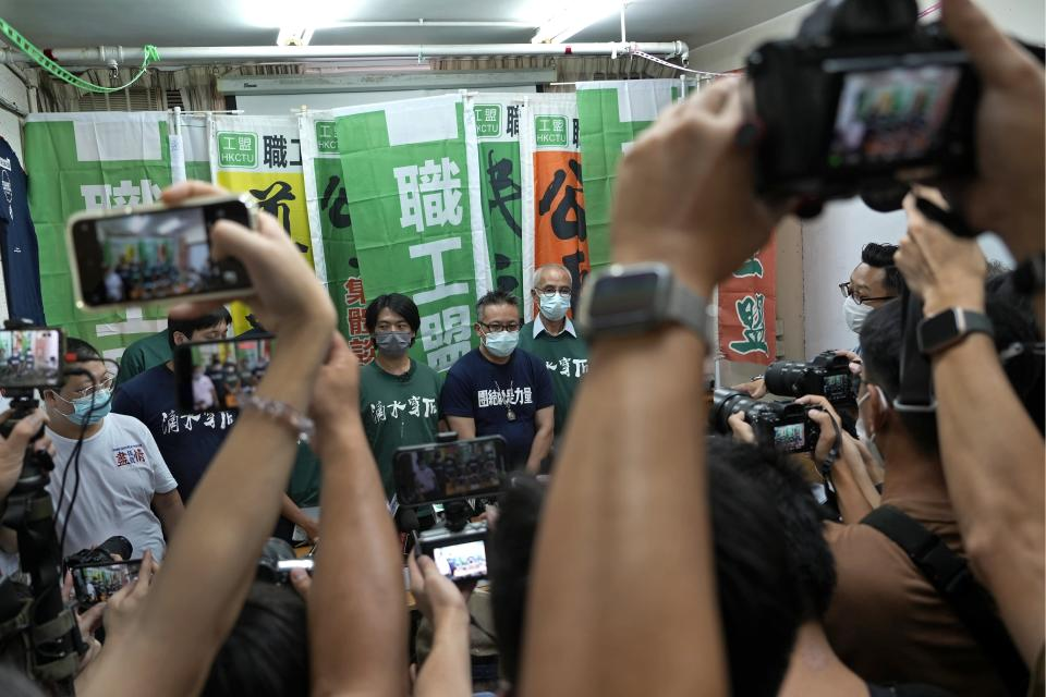 Hong Kong Confederation of Trade Unions President Joe Wong Nai-yuen, center with deep blue T-shirt, poses with other members before a news conference on the possibility of disbandment in Hong Kong, Sunday, Sept. 19, 2021. (AP Photo/Vincent Yu)