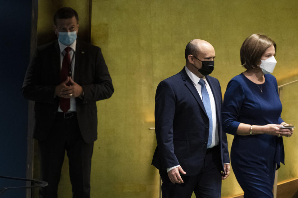Israel's prime minister Naftali Bennett, center, is escorted to the podium before addressing the 76th Session of the United Nations General Assembly, Monday, Sept. 27, 2021, at U.N. headquarters. (AP Photo/John Minchillo, Pool)