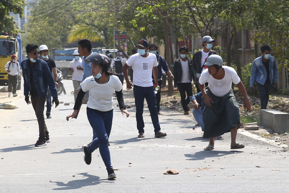 Protesters run as police fire tear gas during a protest against the military coup in Mandalay, Myanmar, Sunday, Feb. 28, 2021. Security forces in Myanmar used lethal force as they intensified their efforts to break up protests a month after the military staged a coup. At least four people were reportedly killed on Sunday. (AP Photo)
