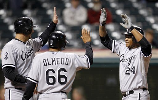 Chicago White Sox's Dayan Viciedo, right, is congratulated by A.J. Pierzynski, left, and Ray Olmedo after Viciedo hit a grand slam in the ninth inning of a baseball game, Monday, Oct. 1, 2012, in Cleveland. Pierzynski, Olmedo and Jordan Danks scored. The White Sox won 11-0. (AP Photo/Tony Dejak)