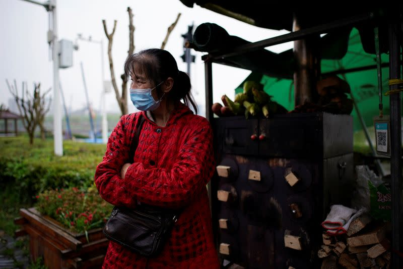 Li Yu wears a face mask at an ancient city wall in Jingzhou, after the lockdown was eased in Hubei