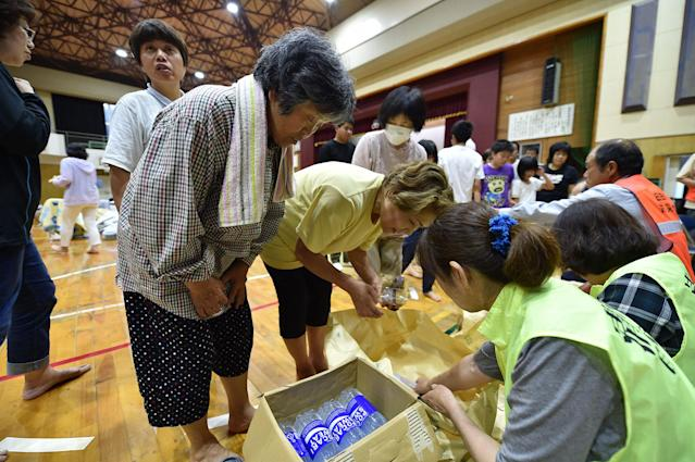 <p>Evacuated residents from a flooded area receive food aid at a school in Hita, Oita prefecture on July 6, 2017.<br> (Photo: Kazuhiro Nogi/AFP/Getty Images) </p>