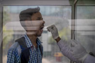 A health worker takes a swab sample to test for COVID-19 at a government hospital in Noida, a suburb of New Delhi, India, Wednesday, April 7, 2021. India hits another new peak with 115,736 coronavirus cases reported in the past 24 hours with New Delhi, Mumbai and dozens of other cities imposing night curfews to check the soaring infections. (AP Photo/Altaf Qadri)