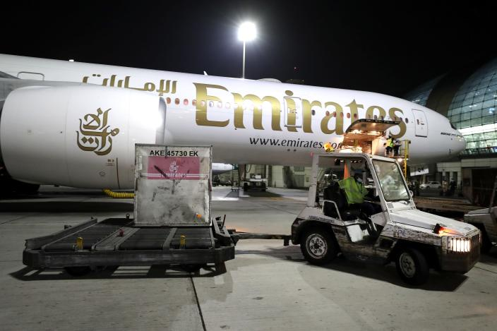 A Pfizer-BioNTech COVID-19 coronavirus vaccine shipment is offloaded from an Emirates Airlines Boing 777 that arrived from Brussels to Dubai International Airport in Dubai, United Arab Emirates, early Sunday, Feb. 21, 2021. As the coronavirus pandemic continues to clobber the aviation industry, Emirates Airlines, the Middle East's biggest airline is seeking to play a vital role in the global vaccine delivery effort. (AP Photo/Kamran Jebreili)