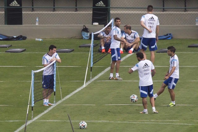 Argentina's Lionel Messi, left, talks to teammates Sergio Aguero, right, and Ezequiel Lavezzi, second right, during a training session in Vespesiano, near Belo Horizonte, Brazil, Friday, July 11, 2014. On Sunday, Argentina faces Germany for the World Cup final soccer match in Rio de Janeiro. (AP Photo/Victor R. Caivano)