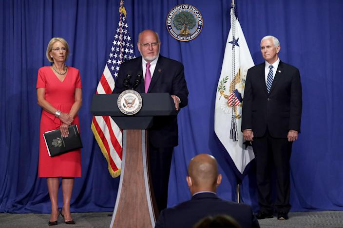 CDC Director Robert Redfield, Secretary of Education Betsy DeVos, and Vice President Mike Pence stand behind a podium at a press conference.