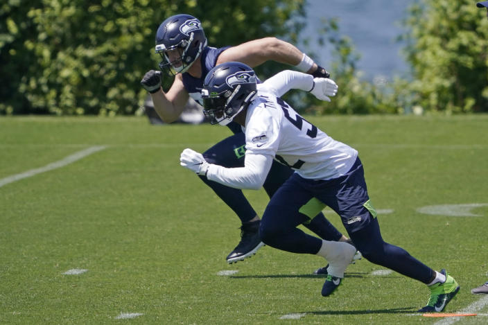 Seattle Seahawks defensive end Darrell Taylor, right, runs a drill with tight end Will Dissly, left, during NFL football practice Wednesday, June 16, 2021, in Renton, Wash. (AP Photo/Ted S. Warren)