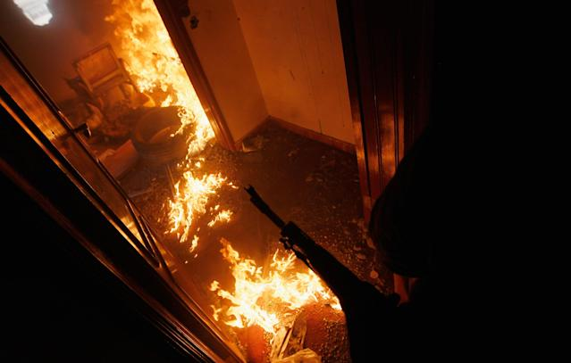 <p>A Libyan rebel fighter covers a burning room containing ensconced government loyalist troops who were firing on them during house-to-house fighting on Tripoli Street in downtown Misrata April 20, 2011 in Misrata, Libya. (Photo by Chris Hondros/Getty Images) </p>