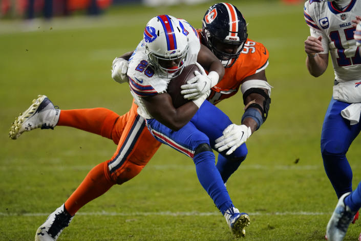 Buffalo Bills running back Devin Singletary runs with the ball as Denver Broncos defensive end Shelby Harris defends during the second half of an NFL football game Saturday, Dec. 19, 2020, in Denver. (AP Photo/David Zalubowski)
