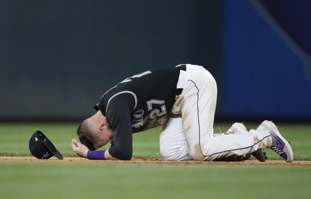 Colorado Rockies shortstop Trevor Story falls to the infield after taking a ground ball to the face on a single by San Diego Padres' Hunter Renfroe during the eighth inning of a baseball game Friday, June 14, 2019, in Denver. (AP Photo/David Zalubowski)